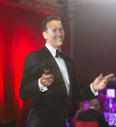 Close up photo of Brendan Cole, holding a microphone.